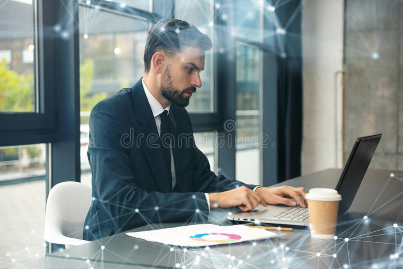 Business man works with laptop on the desk in a modern office near window. Network effects. Working in office. Business concept with network effects stock image