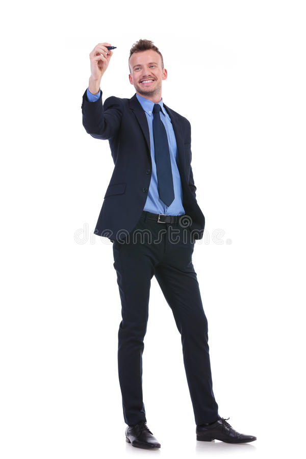 Business man writes on imaginary screen. Full length picture of a young business man writing something on an imaginary screen while holding his other hand in his stock photos