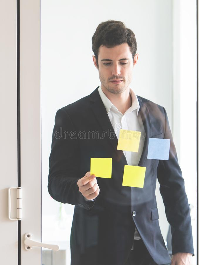 Business man writing idea on to post it windows for plan. Business man is writing idea on to post it windows for plan royalty free stock photo