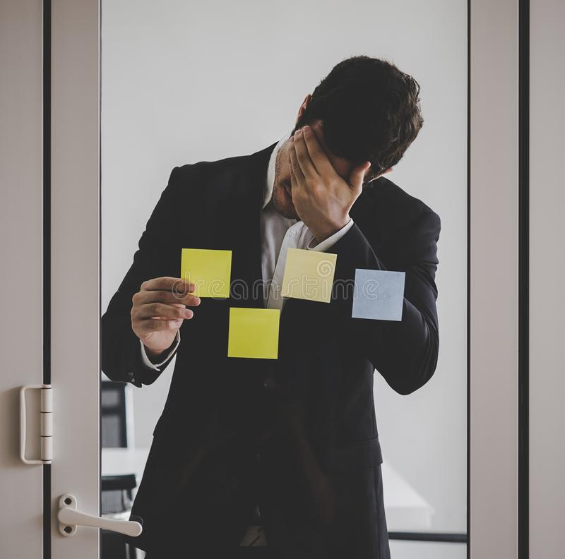 Business man writing idea on to post it windows for plan. Business man is writing idea on to post it windows for plan stock photography