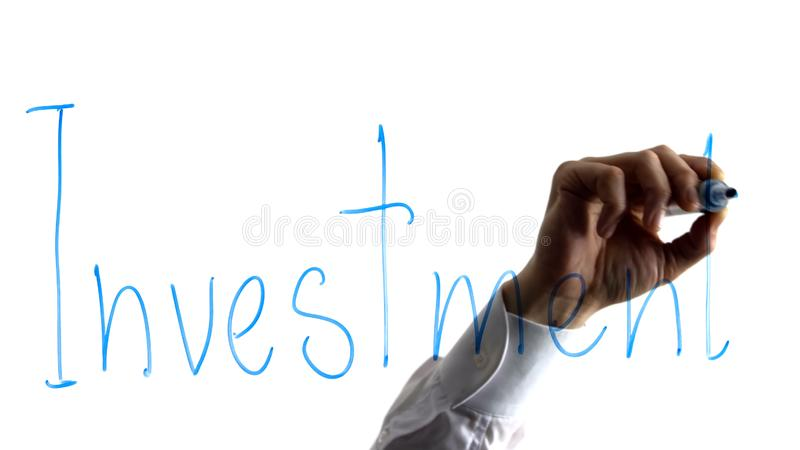 Business man writing investment word on glass, getting money to increase profit. Stock photo stock photography
