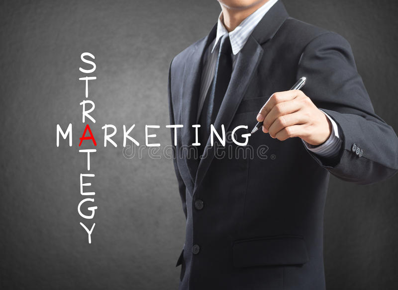 Business man writing marketing strategy concept. By crossword royalty free stock images