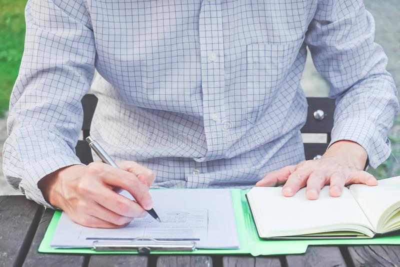 Business man writing notes in personal notebook with right hand, working in the park in front of office building stock photo