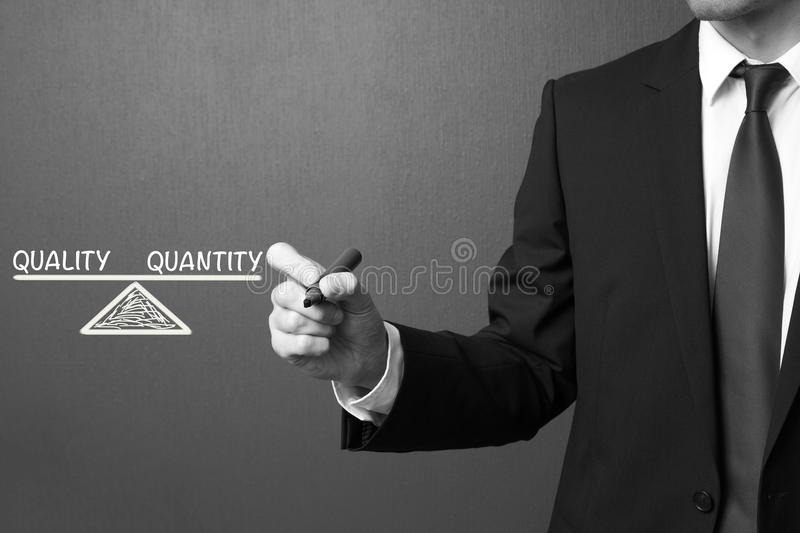 Business man writing Quality and Quantity - Balance Concept stock photo