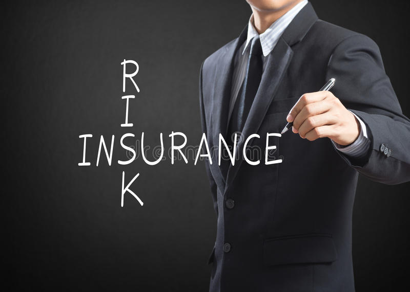 Business man writing Risk Insurance. Crossword stock photo