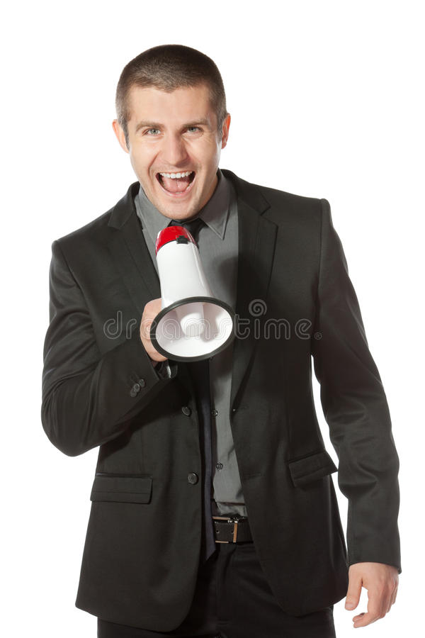 Business man yelling into a megaphone. Portrait of a young business man yelling into a megaphone royalty free stock photography