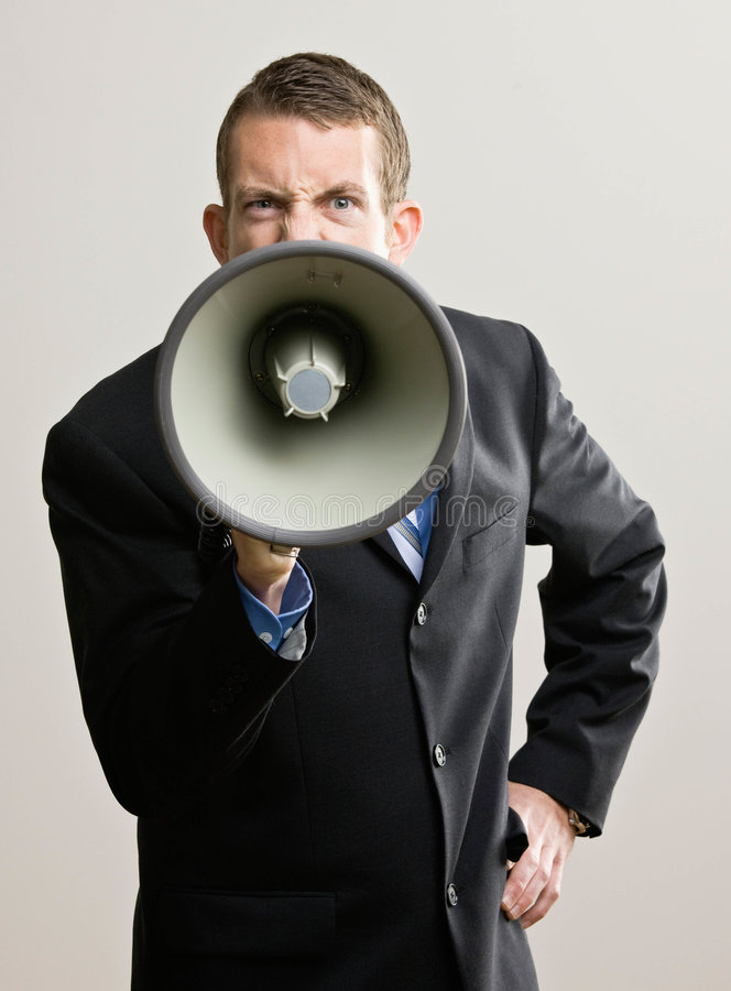Business man yells into megaphone. Angry businessman shouting instructions into megaphone royalty free stock images