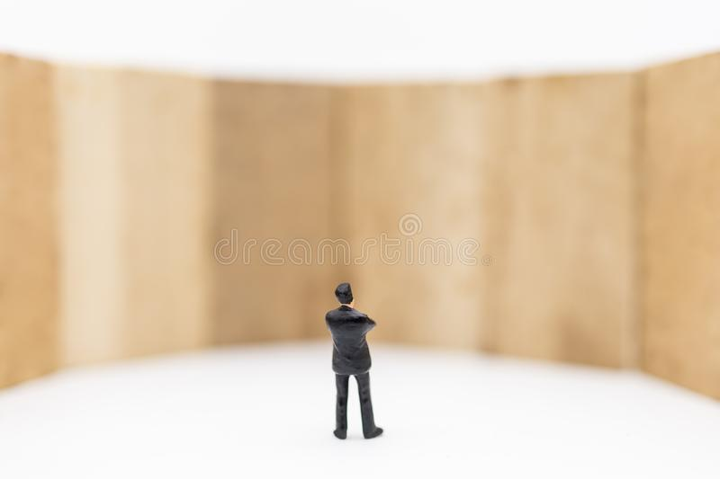 Business, Management and Planning Concept. Close up of businessman miniature figure standing and looking to wooden block toy wall. On white background and stock photography