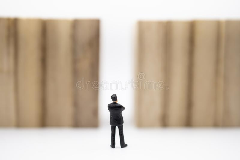 Business, Management, Planning, Succession and strategy Concept. Close up of businessman miniature figure standing in front of. Wooden block wall on white royalty free stock photography