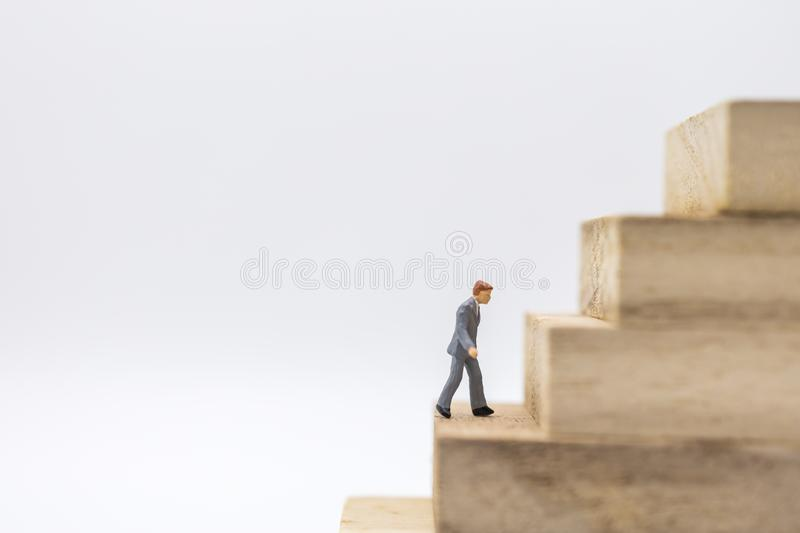 Business, Management Planning and Work concept. Close up of businessman miniature figure walking to top of stack of wooden block. Toy on white background and stock images