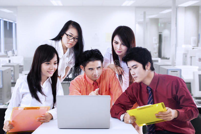 Business manager explains to team in office. Business manager is explaining his plan to team in the office stock image