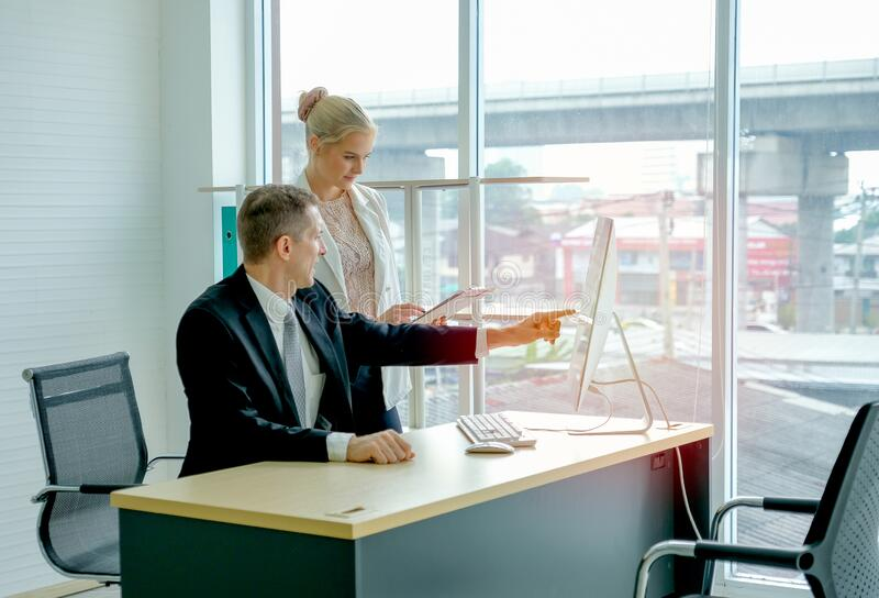 Business manager man point to the screen and discuss with his secretary in the office with glass window royalty free stock images