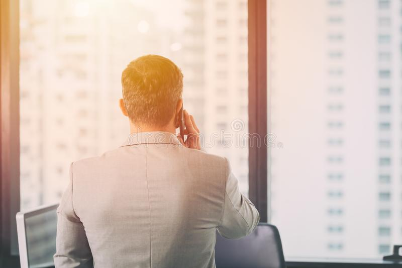 Business manager phone call and looking out at windows royalty free stock photography