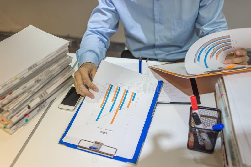 Business Manager porównuje dwa sprzedaż raportu obrazy stock