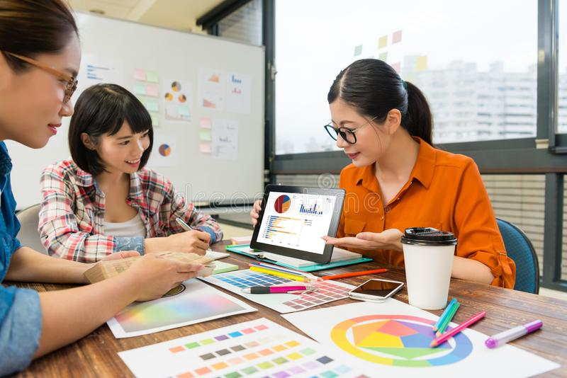 Business manager using mobile digital tablet. Elegant beauty female business manager using mobile digital tablet showing company marketing analysis document for stock photography