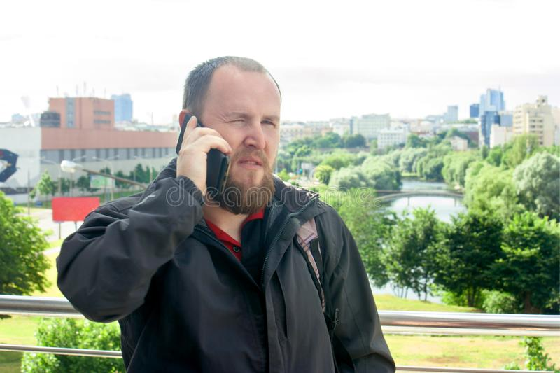 Business mature male tourist with a beard talking on the phone royalty free stock photos