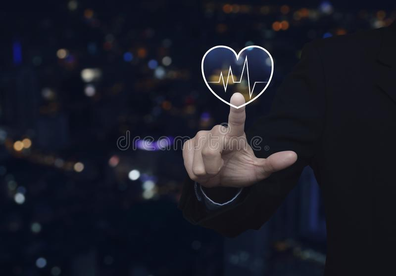 Business medical health care service concept. Businessman pressing heart beat pulse flat icon over blur colorful night light city tower and skyscraper, Business royalty free stock images