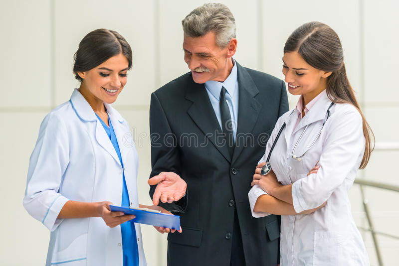 Business & medicine. Patron. Senior male businessman shakes hands doctors in hospital royalty free stock image