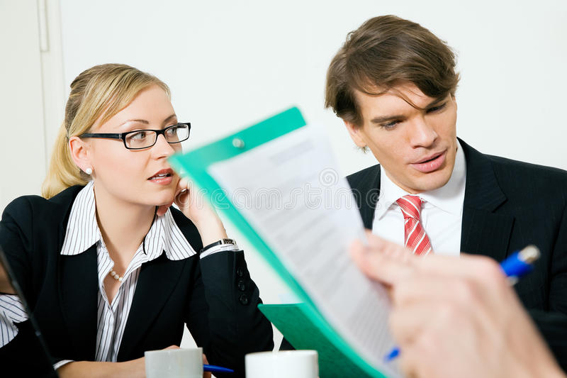 Business meeting. Two businesspeople (male / female) in a meeting, documents - probably a vendor's bid - are being discussed stock images