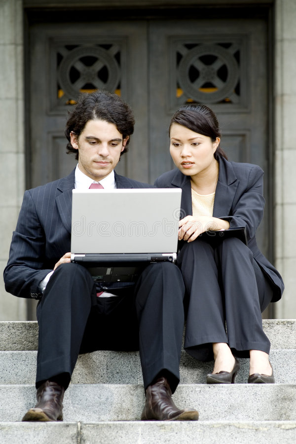 Business Meeting. A pair of business people meeting on the steps of an old building stock image