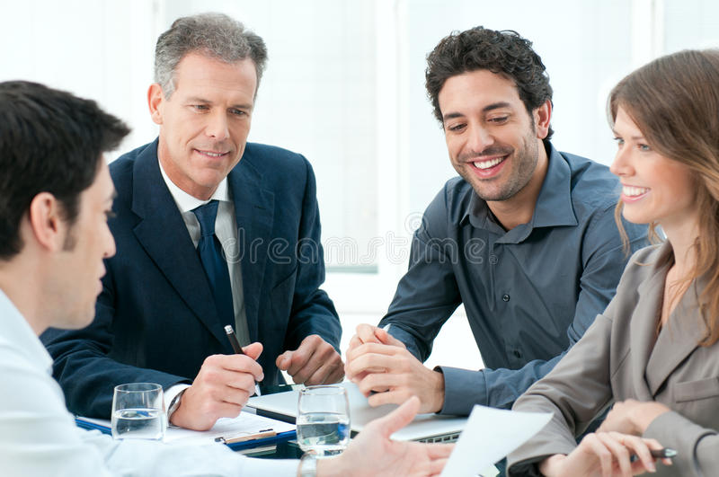 Business meeting. Happy business people discussing together their strategy at meeting in office stock images