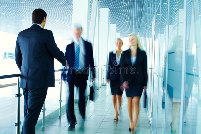 Business meeting. Business people meeting each other in the office corridor and shaking hands royalty free stock photo