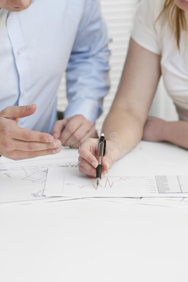 Business Meeting. A businesswoman and a businessman in a meeting. Teamwork. Pointing and looking at a printed diagram on a table stock photos