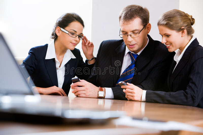 Business meeting. Image of business people sharing info on mobile phones stock photo