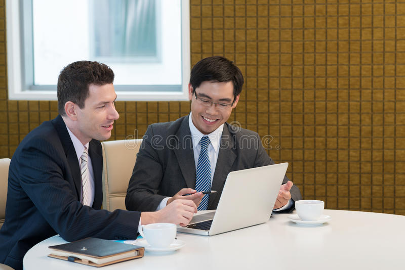 Business meeting. Asian businessman showing something on the laptop to his Caucasian partner stock photography