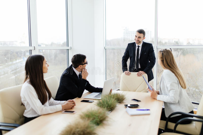 Business meeting. Business people in formalwear discussing something while sitting together at the table stock images