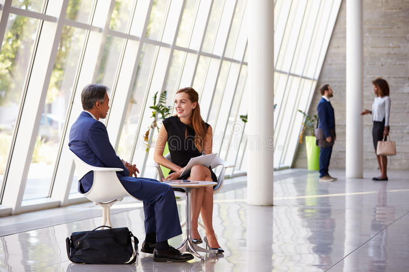 Business Meeting In Busy Office Foyer Area stock photography