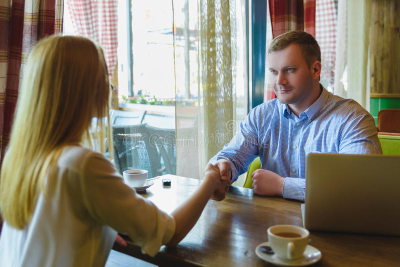 Business meeting in a cafe. Woman and man made a deal royalty free stock photos