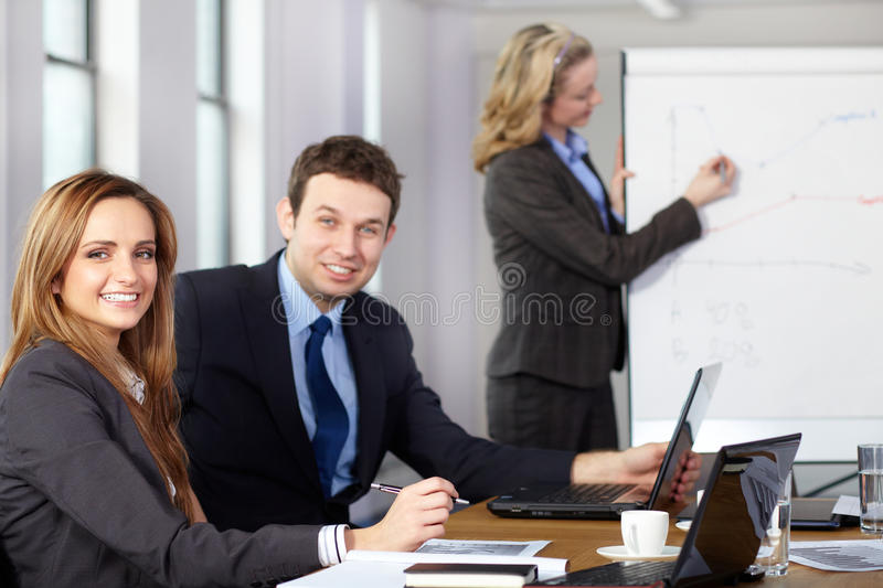 Business meeting, female presents graphs. Business meeting, two colleagues on foreground while blonde female presents graph on flipchart on the background royalty free stock photo