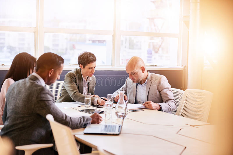 Business meeting between four professional executives in conference room stock image