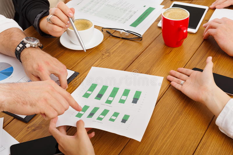 Business meeting. Hands closeup with diagram papers. Business meeting. Hands closeup at modern office workplace, wooden desk. Team discussion, data analysing stock photo