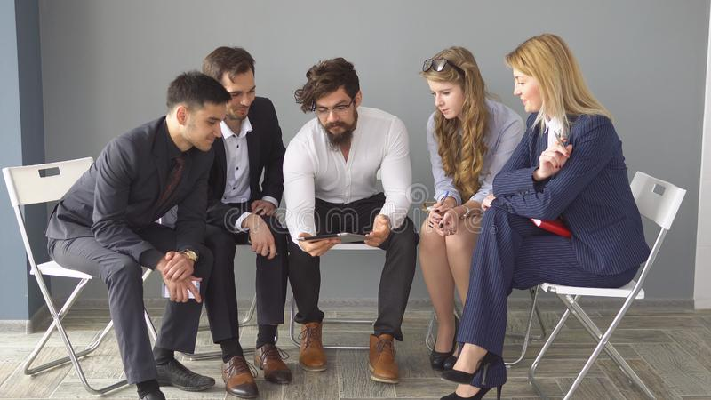 Business meeting in an informal setting. young entrepreneur show information to colleagues on the screen of the tablet. PC royalty free stock image