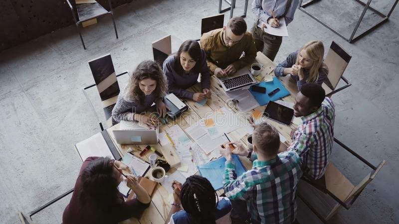 Business meeting at loft shared space. Multiethnic team talking, woman manager giving direction to people. Top view. stock photos