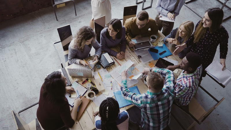 Business meeting at loft shared space. Multiethnic team talking, woman manager giving direction to people. Top view. royalty free stock photo