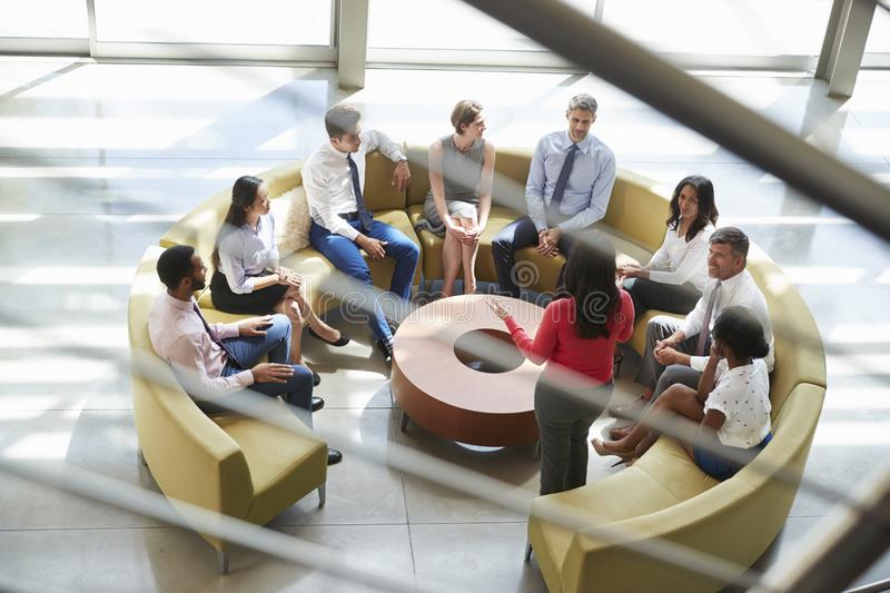 Business meeting in a lounge area, seen through stair rail stock photos