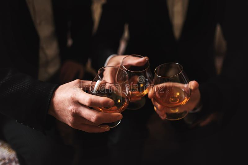 Business meeting. Men hold glasses of whiskey. Men`s Party. Hand with a drink of alcohol royalty free stock image