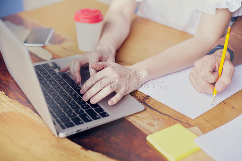 Business meeting in modern office, close-up of woman hands on keyboard laptop on wooden table, man hand writing by pencil. royalty free stock photos