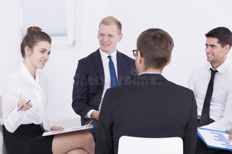 Business meeting in a nice atmosphere. Group of businesspeople sitting in a circle during meeting, light interior royalty free stock photos