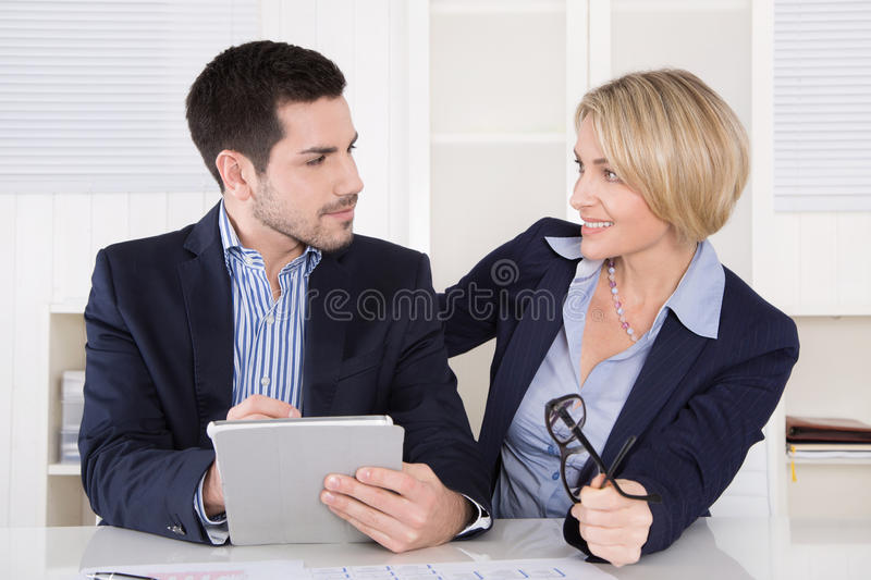 Business meeting: professional successful team; managing director and assistant with tablet computer at the office. Also flirting royalty free stock image