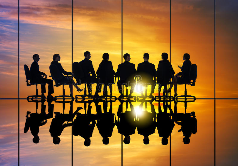 Business meeting. Silhouettes of group of business people against sunset stock photography