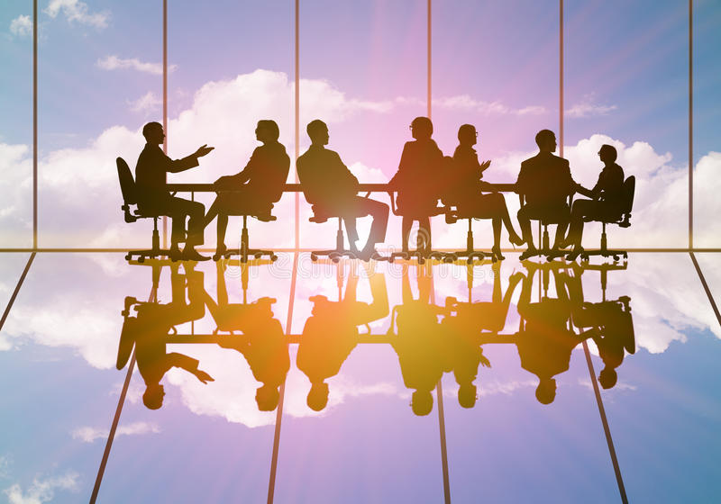 Business meeting. Silhouettes of group of business people against sunset stock image