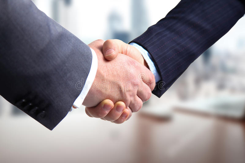 Business meeting at the table shaking hands conclusion of the contract.  royalty free stock photo