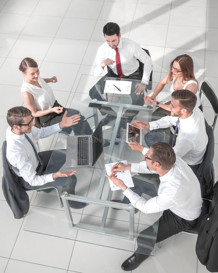 Business meeting at the table, top view. High angle view of multi-ethnic business people discussing in board room meeting royalty free stock photo