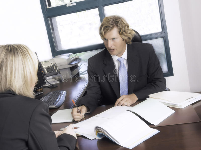 Business Meeting Between Team Members. Two business professionals meet in an office at a desk to review files and papers, and to discuss a transaction both have stock photos
