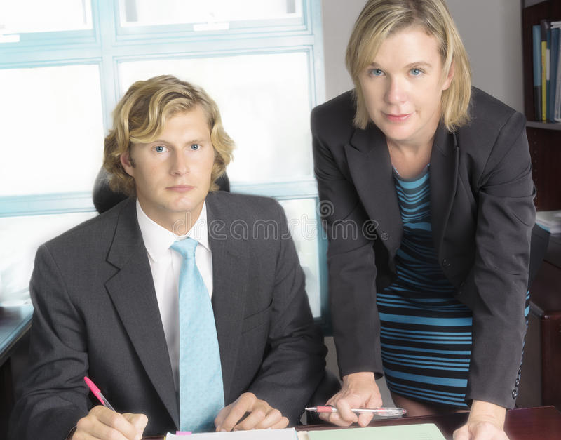 Business Meeting Between Team Members. Two business professionals meet in an office to review accounting files and papers royalty free stock photo