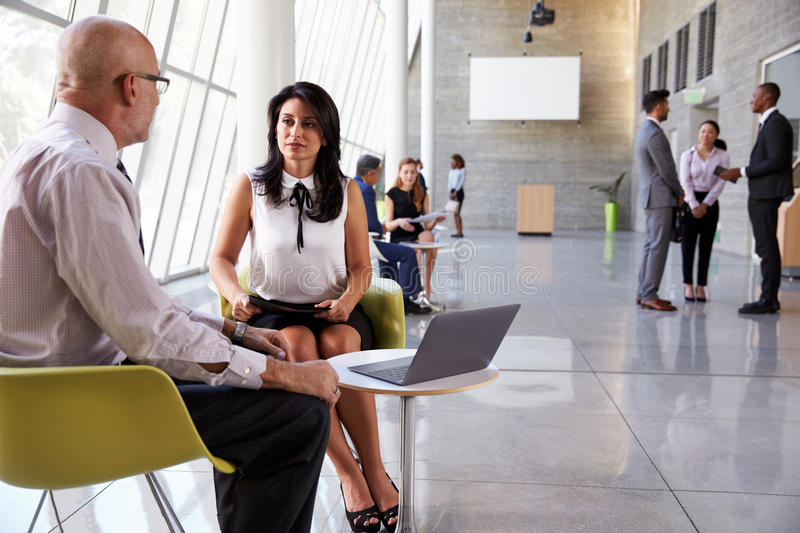 Business Meetings In Busy Office Foyer Area stock photography